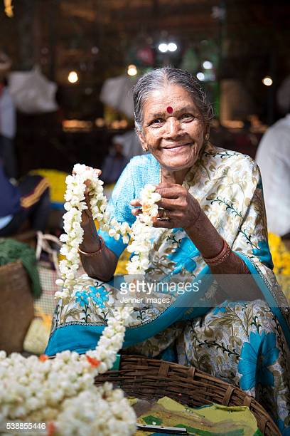 Portrait of a female Indian trader at a city flower market.