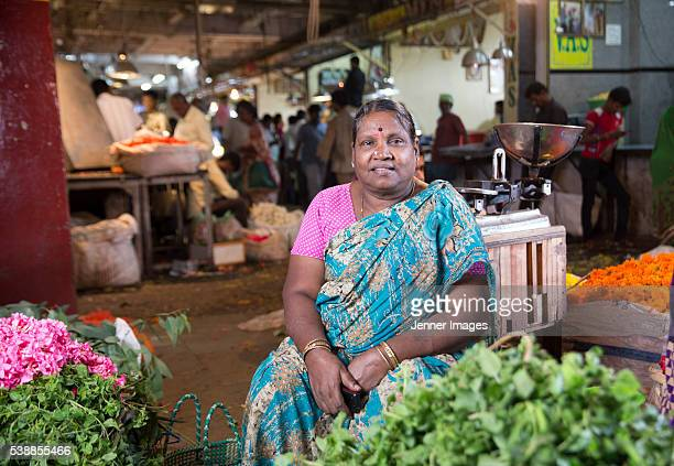 portrait of a female indian trader at a city flower market. - vendor stock pictures, royalty-free photos & images