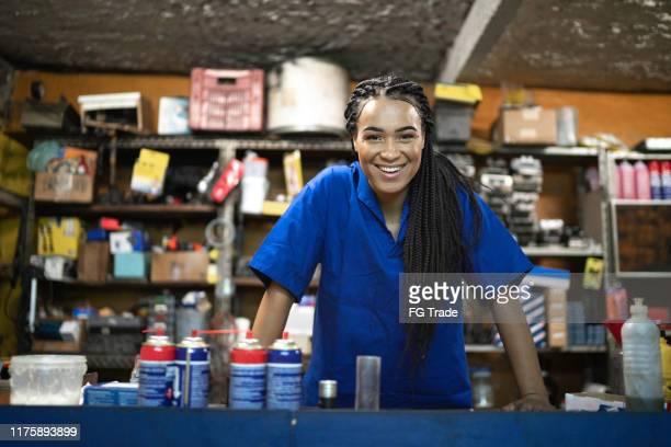 retrato de um mecânico fêmea que está atrás de de contador em uma auto loja de reparo - pequeno - fotografias e filmes do acervo
