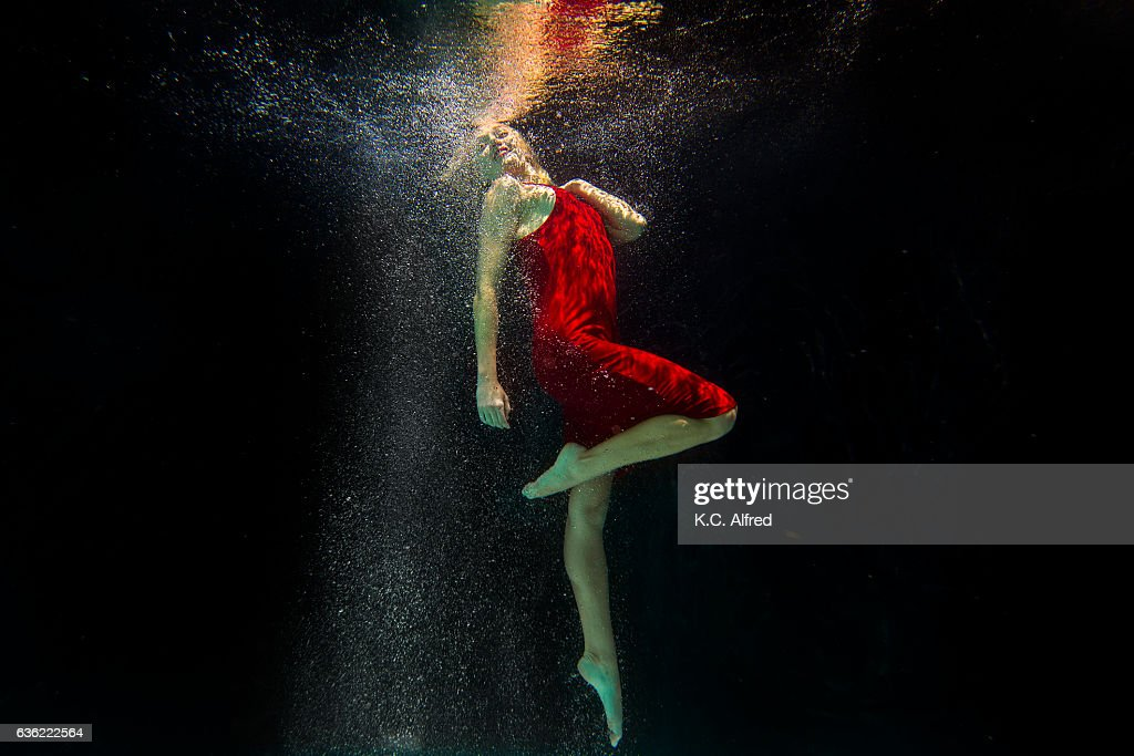 Portrait of a female model underwater in a swimming pool with a black background in San Diego, California. : Stock Photo