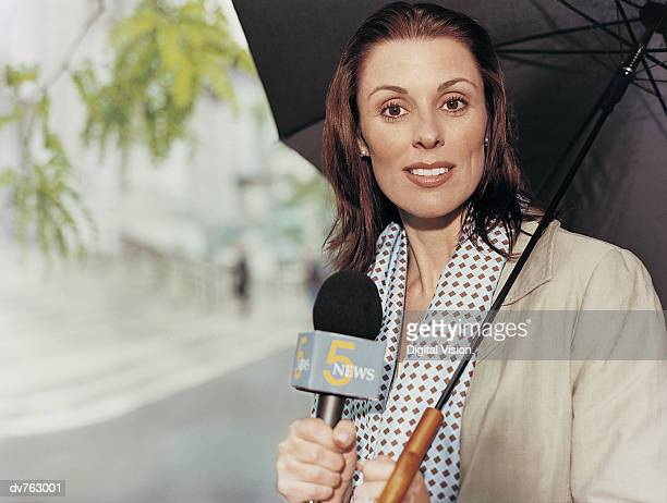 Portrait of a Female News Reporter Holding an Umbrella and a Microphone