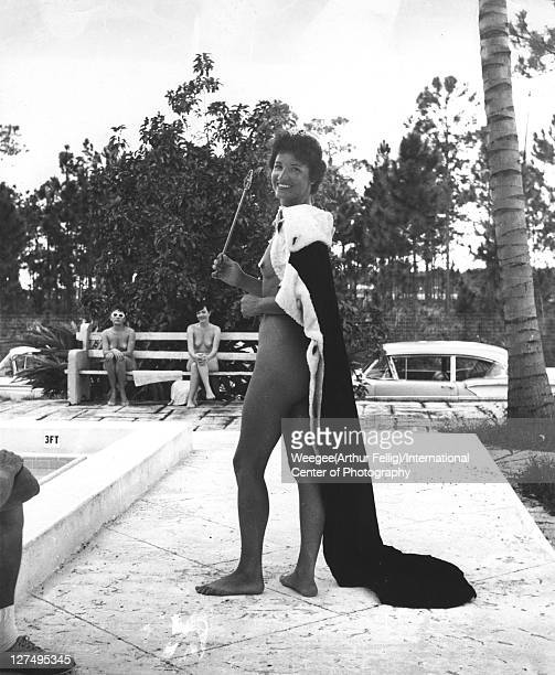 Portrait of a female nudist in a crown and cape a staff in her hand as she poses a swimming pool at an unidentified camp mid 20th century Photo by...
