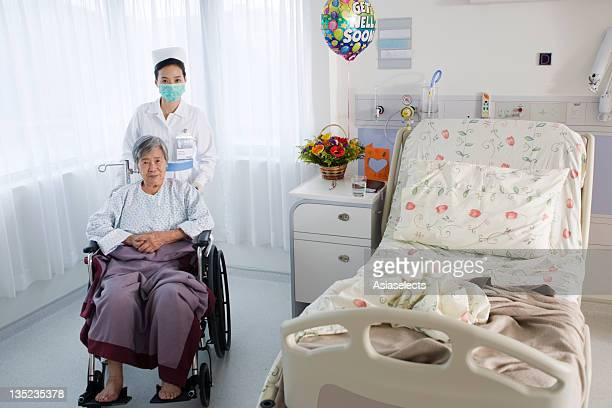 portrait of a female nurse taking care of a female patient - women tied to bed stock photos and pictures