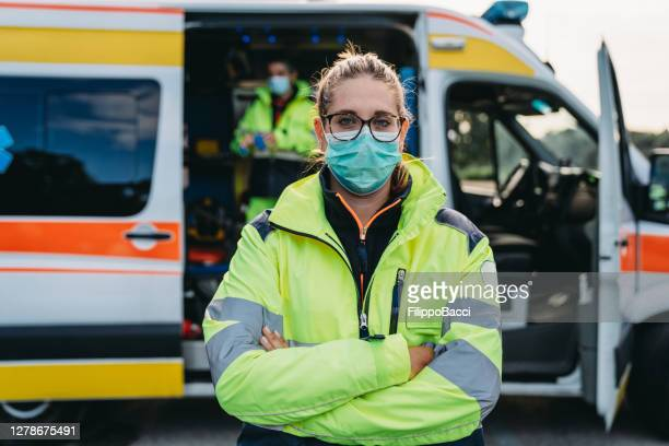 portrait of a female paramedic in front of an ambulance outdoor - essential services stock pictures, royalty-free photos & images