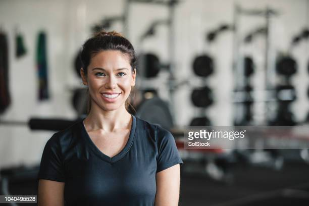 portrait of a female personal trainer in the gym - fitness instructor stock pictures, royalty-free photos & images