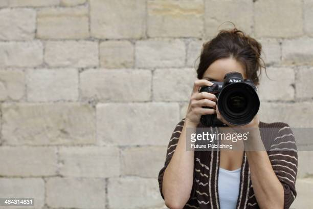 Portrait of a female photographer looking through the viewfinder of a Nikon D3 DSLR while on location in Bath, England, taken on August 14, 2013.