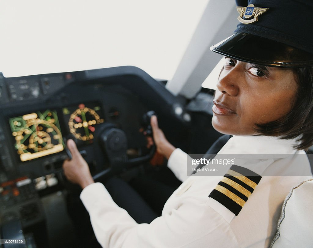 Portrait of a Female Pilot Sitting in the Cockpit : Stock Photo