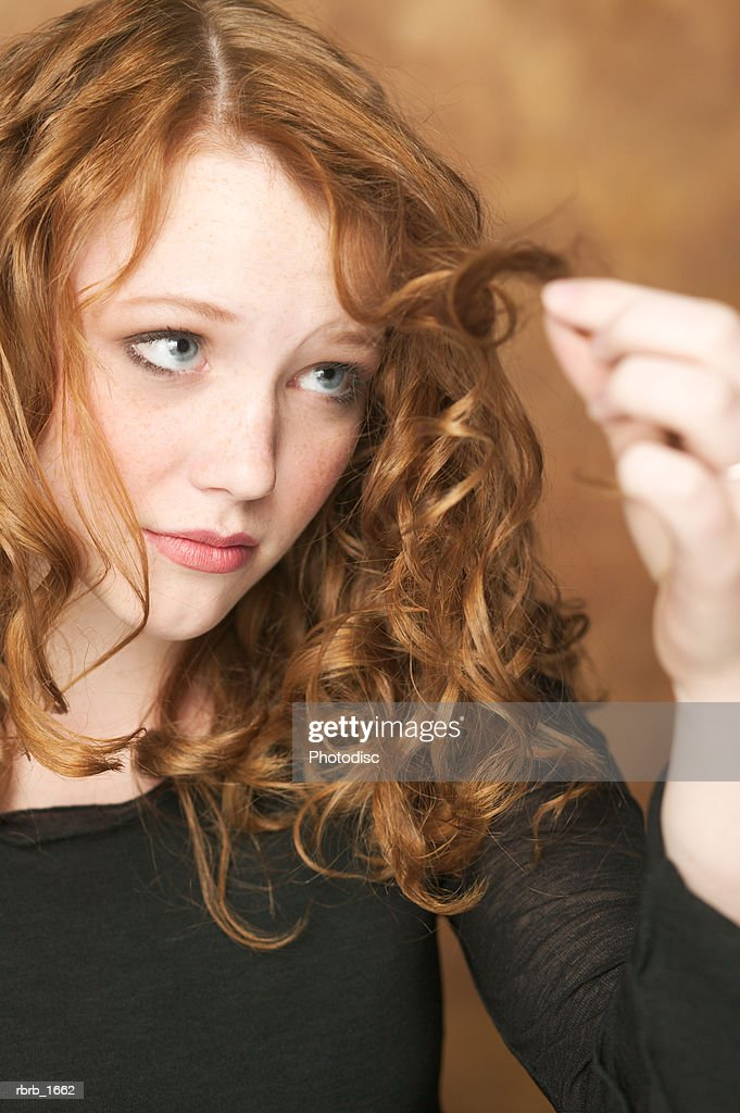 portrait of a female redheaded teen in a black shirt as she examines the end of her curls : Stockfoto