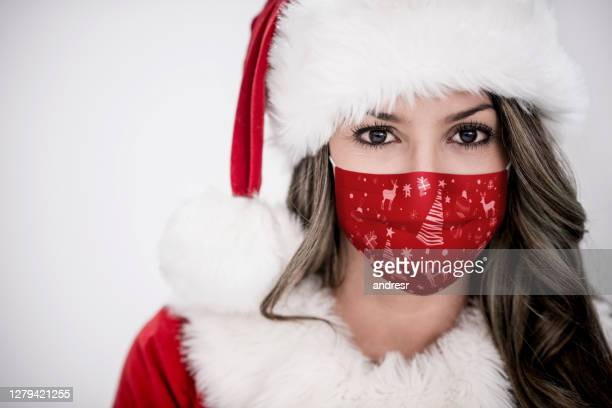 portrait of a female santa wearing a christmas facemask - father christmas stock pictures, royalty-free photos & images