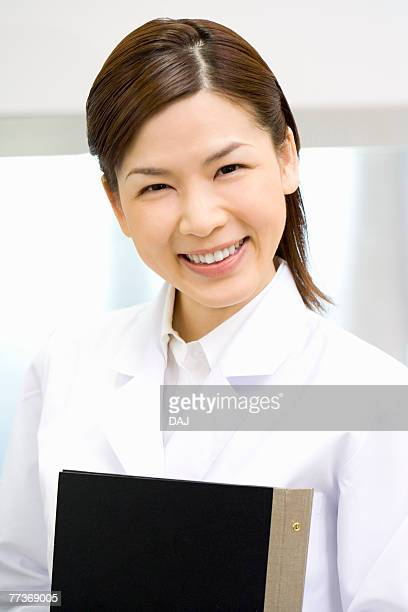 Portrait of a female scientist, smiling and looking at camera, front view