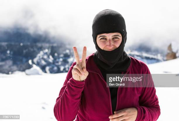 portrait of a female snowboarder showing peace sign at cerro catedral - バラクラバ ストックフォトと画像
