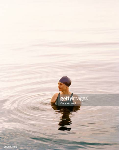 portrait of a female swimmer in the sea at sunset - swimming stock pictures, royalty-free photos & images