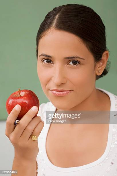portrait of a female teacher holding an apple and smiling - hair part stock pictures, royalty-free photos & images