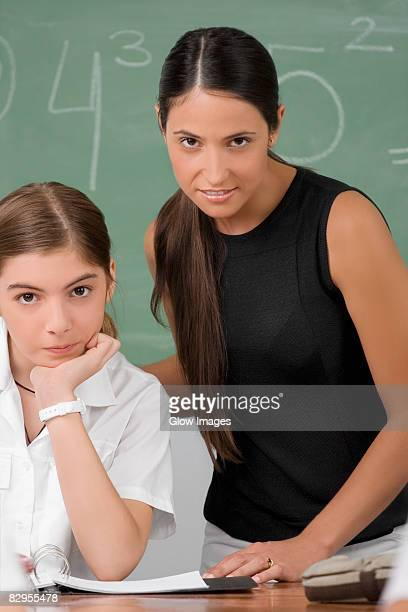 Portrait of a female teacher with a schoolgirl in a classroom