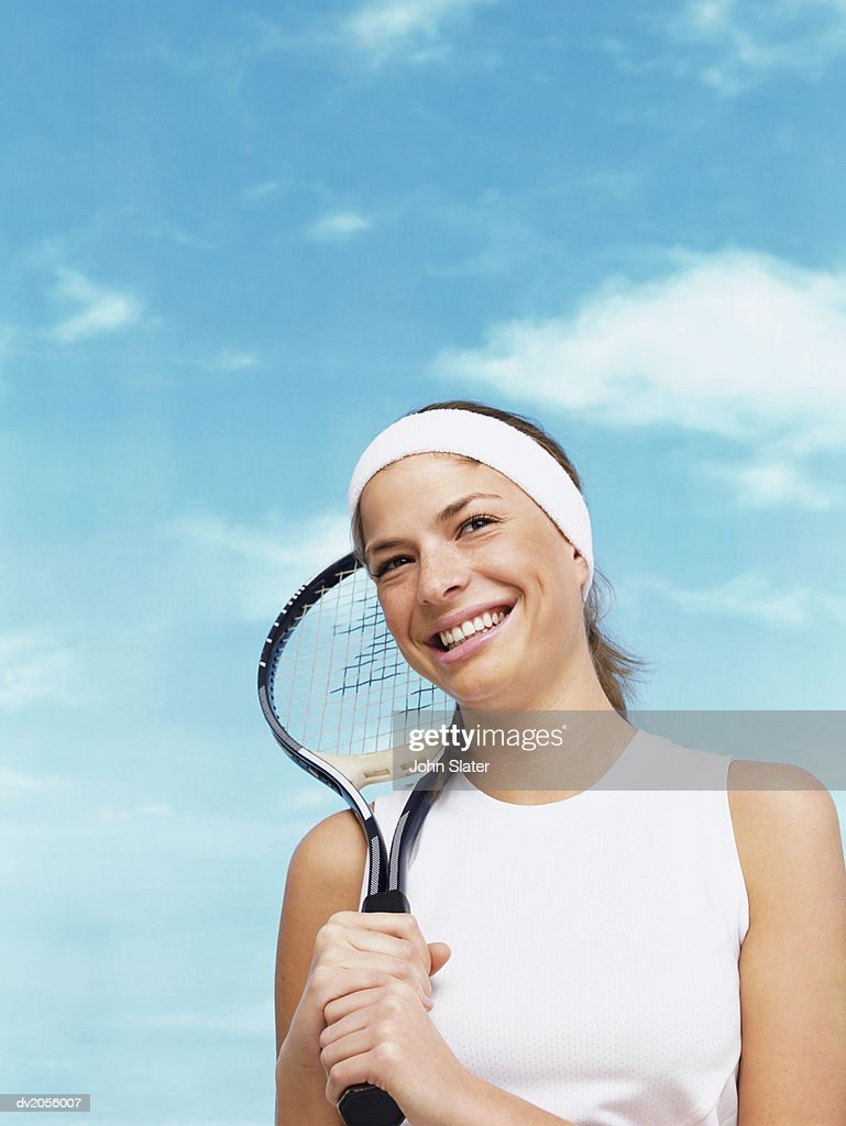 Portrait of a Female Tennis Player Holding a Tennis Racket Against Her Shoulder : Stock Photo