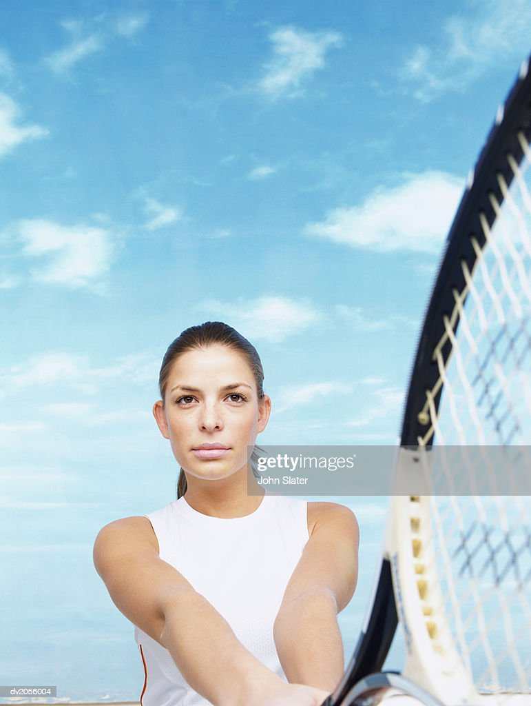 Portrait of a Female Tennis Player Holding a Tennis Racket : Stock Photo
