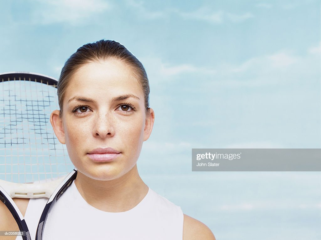 Portrait of a Female Tennis Player with Her Tennis Racket on Her Shoulder : Stock Photo