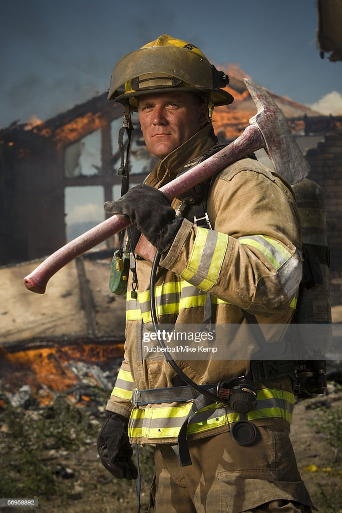 Portrait of a firefighter holding an axe : Foto de stock