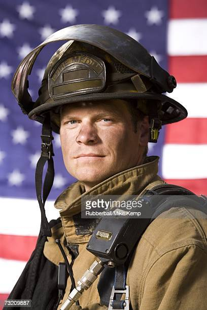 portrait of a firefighter with us flag - firefighter's helmet stock photos and pictures