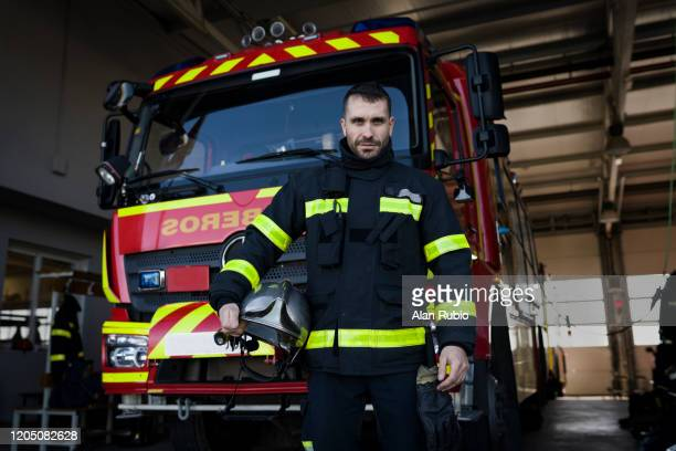 portrait of a fireman posing proudly in front of his truck waiting for the call. - rescue worker stock pictures, royalty-free photos & images