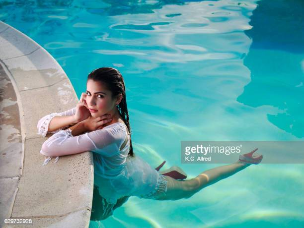 portrait of a fit, female model in a white top relaxes in a swimming pool in san diego, california. - alfred weiss stock-fotos und bilder