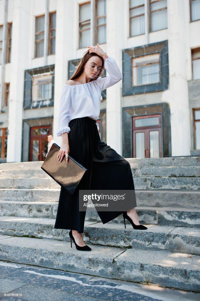 白いブラウス、黒い太線パンツ、背景に巨大な白い建物と彼女の手で黒のノート パソコンと階段でポーズの古典的なハイヒールで完璧な若い女性の肖像画。 : ストックフォト