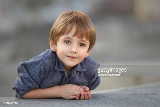 portrait of a friendly looking little boy with brown eyes and blonde hair, looking into the camera - alleen jongens stockfoto's en -beelden