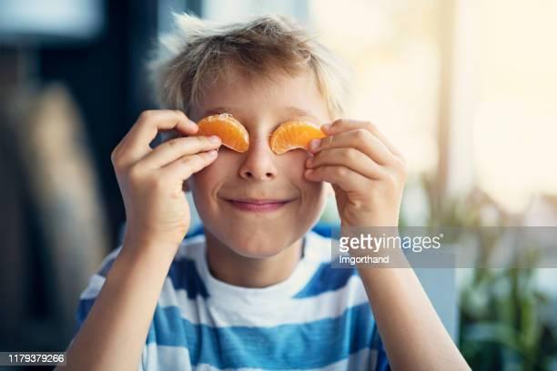 portret van een grappig jongetje dat oranje eet - kindertijd stockfoto's en -beelden