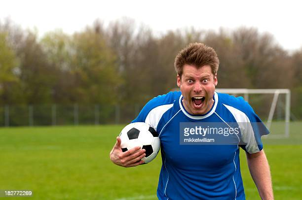 Portrait of a furious soccer player who screams at camera