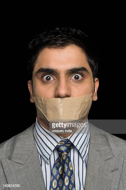portrait of a gagged businessman - eyes wide shut foto e immagini stock