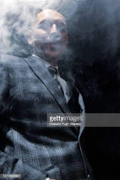 portrait of a gangster smoking an electronic cigarette - howard pugh stock pictures, royalty-free photos & images