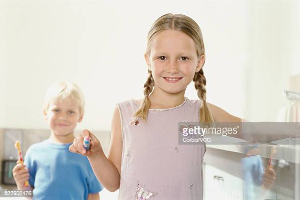 Portrait of a girl and her little brother holding toothbrushes in the bathroom