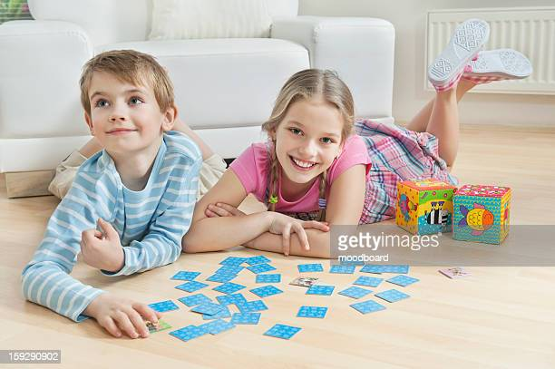 Portrait of a girl and little brother lying on floor with cards