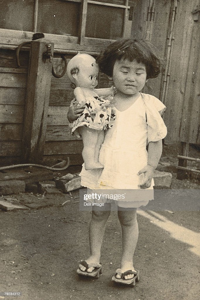Portrait of a girl and plastic doll : Stock Photo