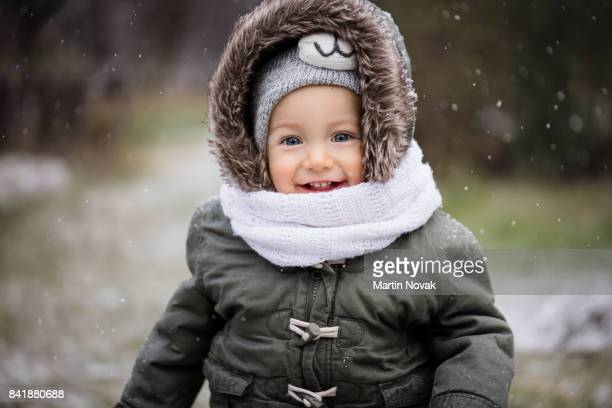 portrait of a girl child playing in snow - coat stock pictures, royalty-free photos & images