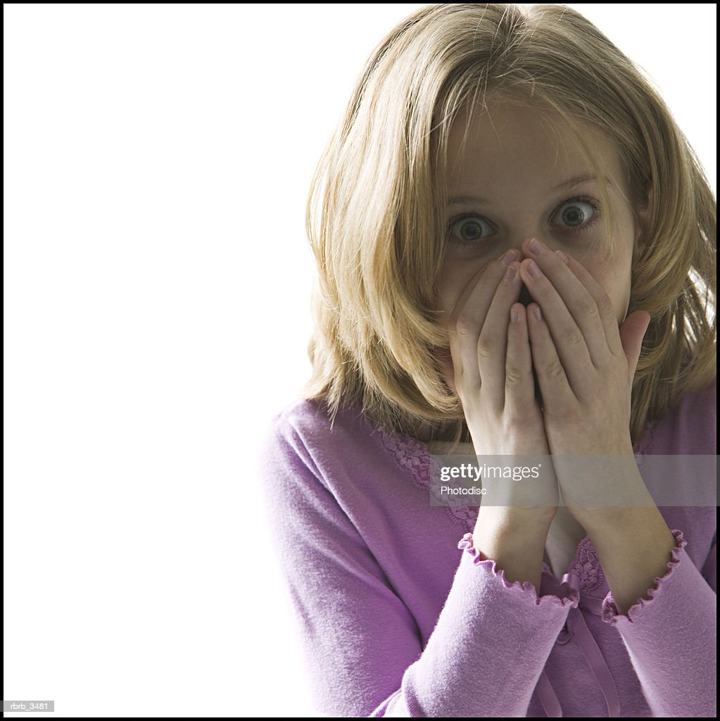 Portrait of a girl (9-10) covering her mouth with her hands : Foto de stock
