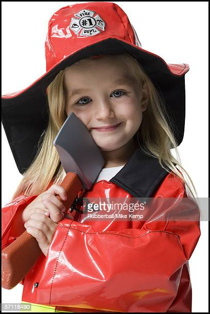 portrait of a girl dressed as a firefighter and holding an axe - fire protection suit - fotografias e filmes do acervo