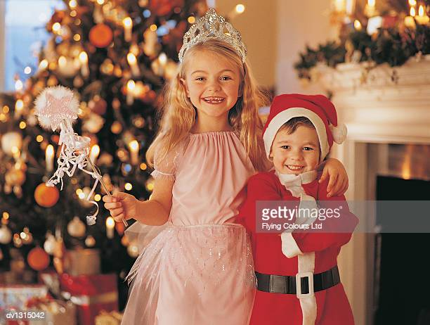 Portrait of a Girl Dressed in a Fairy Costume Standing Beside Her Brother Dressed in a Father Christmas Costume