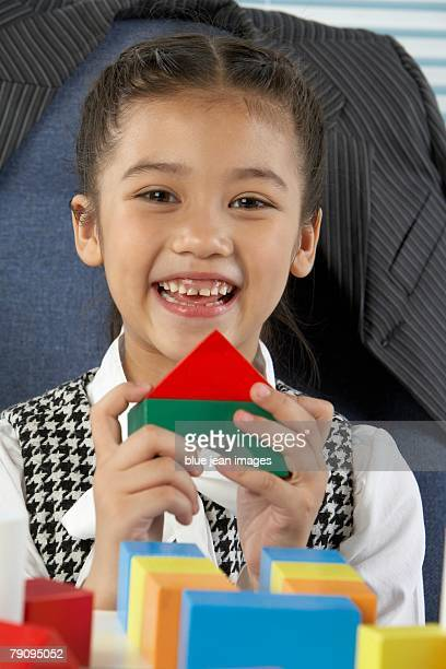 Portrait of a girl dressed in business attire holding colored building blocks in her hands.