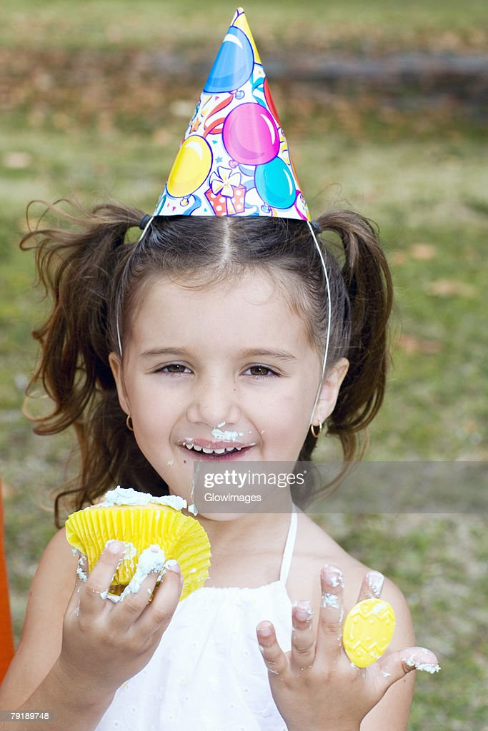Portrait of a girl eating a cupcake : Stock Photo