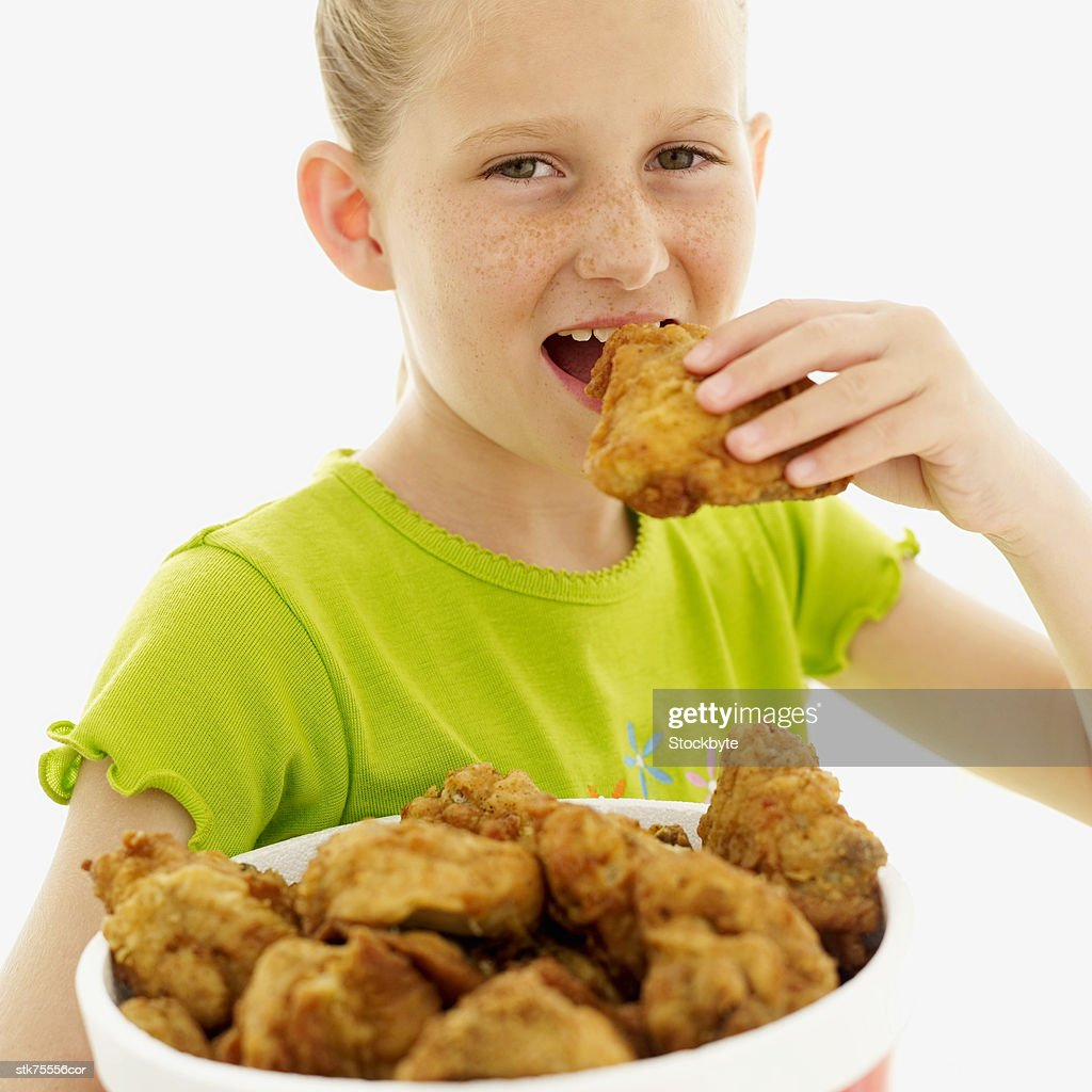 Nuggets Healthy Eats: Portrait Of A Girl Eating Fried Chicken Stock Photo