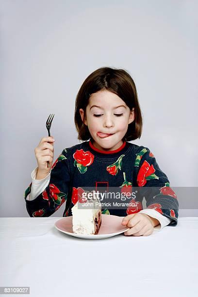 portrait of a girl (8-9) eating piece of cake - lécher photos et images de collection