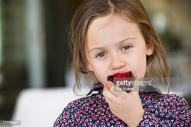 Portrait of a girl eating plum