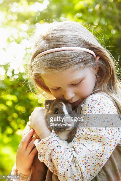 Portrait of a girl (6-7) embracing and caressing her pet rabbit in garden