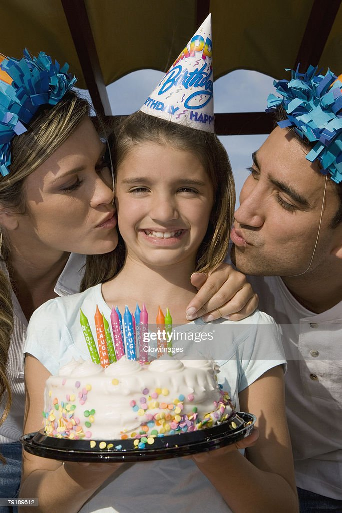 Portrait of a girl holding a birthday cake and her parents kissing her : Foto de stock