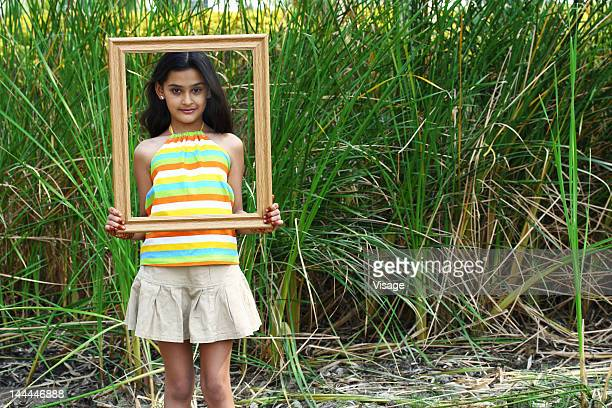 Portrait of a girl holding a frame