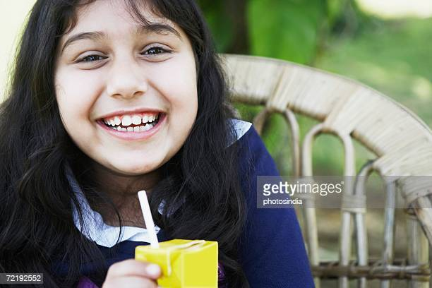 portrait of a girl holding a juice carton - juice carton stock photos and pictures