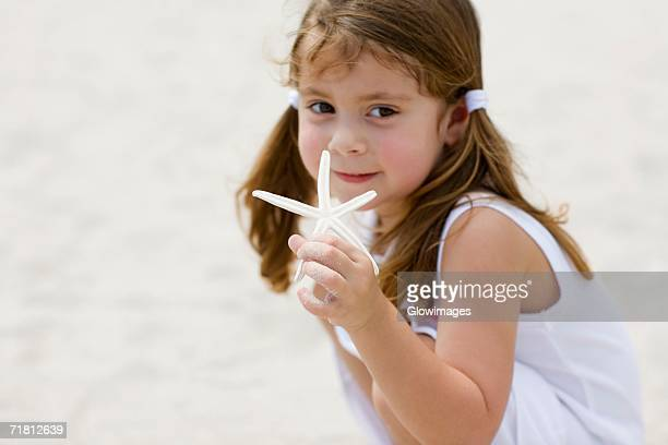 Portrait of a girl holding a starfish