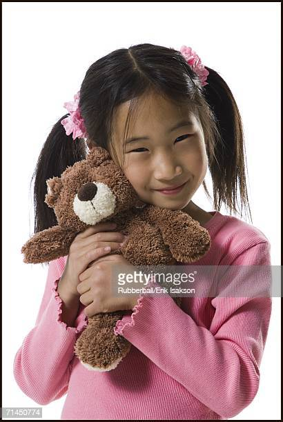 Portrait of a girl holding a teddy bear and smiling