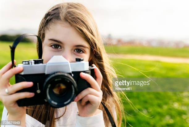 portrait of a girl holding an old-fashioned camera outdoors - camera girls stock photos and pictures